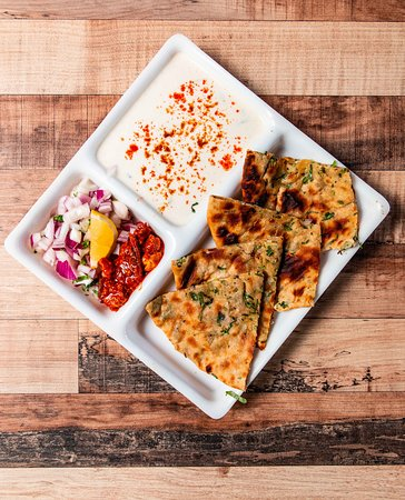 Aloo Prantha - Stuffed whole-wheat flatbread served with yoghurt and pickle.