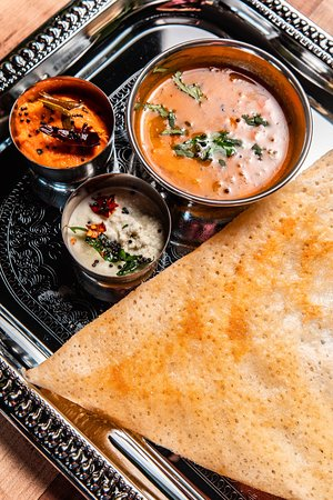 Masala Dosa - Thin layered fermented crepe (dosa) served with lentil based stew, tomato chutney and coconut chutneys.
