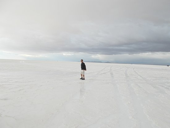 "On a ""wet salar"" with a ""partial reflection"" of me down below (the sixth stop)"