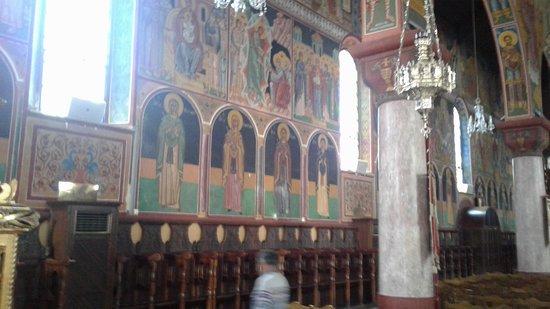 Colourful frescoes along a wall in the church