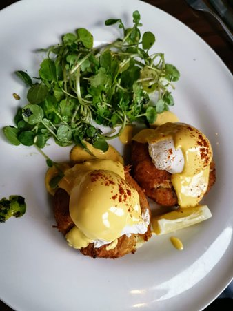 Tasty homemade fishcakes with poached eggs and Hollandaise sauce and watercress