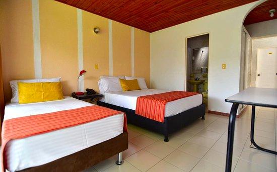 Habitación triple estándar, con ventilador, baño con ducha y balcón con hamaca