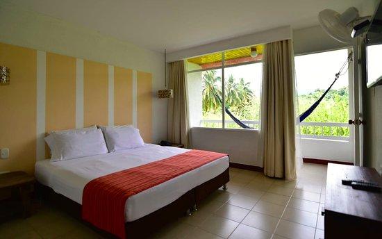 Habitación doble estándar, con ventilador, baño con ducha y balcón con hamaca
