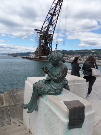 Statue in foreground with crane in background