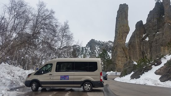 Black Hills Above and Beyond Tours: One of our very nice 9-14 passenger vans on the Needles Highway by one of the spires, totem pole rock.