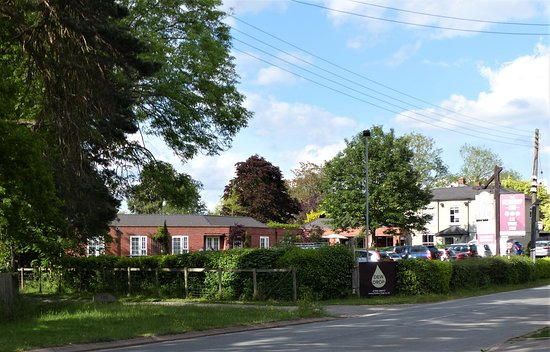 Worcestershire, UK : Photo taken from across the road showing the Dewdrop Inn, car parking, hedged area which contains a grassy area with seating.