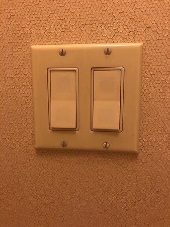 Dirty looking light switches, worn wallpaper
