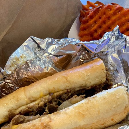 Philly Cheesesteak sandwich with a side of sweet potato fries