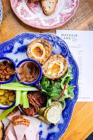 Ploughman's plate; Serrano ham, scotch egg, aged cheddar cheese, pickled onion, house piccalilli, Branston pickle, ciabatta