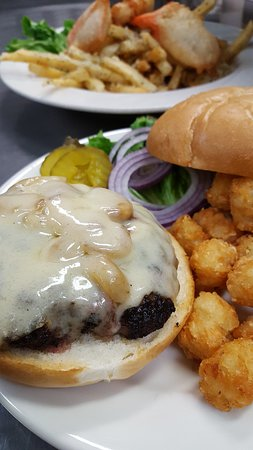Roasted Garlic Burger with provolone and tots. Salmon fish & chips in the background with garlic cheese fries.
