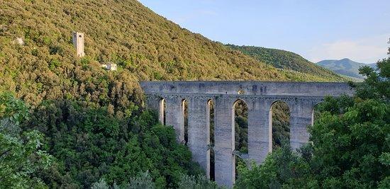Il Ponte al tramonto compiendo il giro della Rocca. Sulla sinistra si vede il fortilizio dei mulini sul Monteluco che al momento non si può raggiungere percorrendo il ponte, chiuso per precauzione dal terremoto del 2016. Giugno 2019