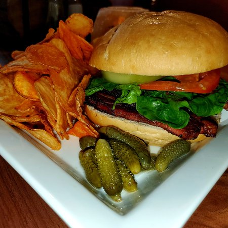 Smoke Pork Belly BLT sandwich with crisp lettuce and the house' signature marinated tomatoes on top of a Kaiser roll.