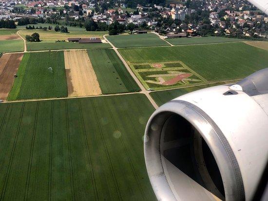 Swiss International Air Lines [SWISS]: Landeanflug auf ZRH  -  über das typische Victorinox - Emblem im Rasen hinweg