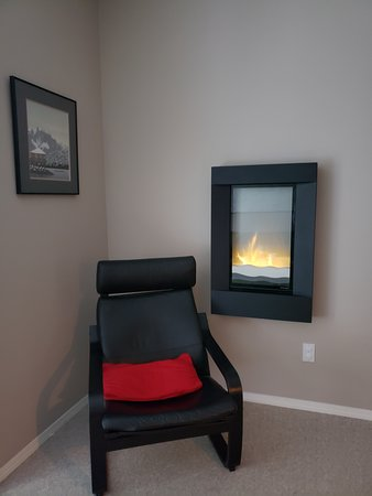 Standing in the living room area looking at the wall fireplace. Very quaint and really added a nice touch.