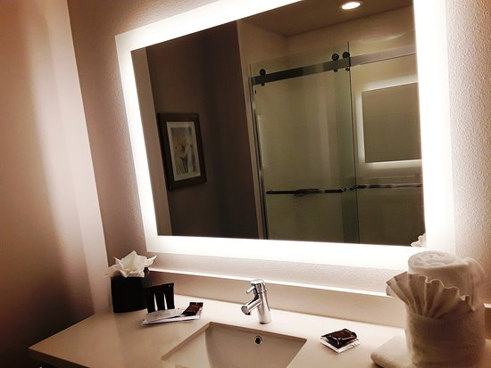 Gorgeous stone vanity, backlit mirror and tile flooring are features of your bathroom.