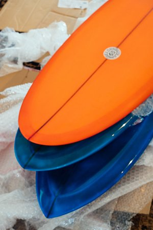 The rack at our store is filled with unique surfboards, manufactured with pride and passion for your personal joy.