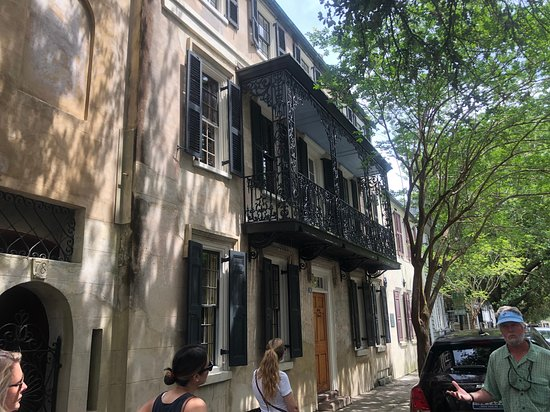 Charleston's Alleys & Hidden Passages Guided Walking Tour: An example of a wrought-iron balcony that survived the Civil War. Most wrought-iron was melted down for use by the Confederate Army. After the war, cast-iron took its place. That's our guide Jim in the blue hat.