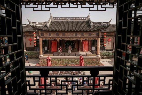 Kunshan, Kina: 绕过走道,进入戏院,属于周庄古戏台全新的一切,终于豁然开朗。院内的长幔,如昆曲韵律一般悠长。寻一处伞下雅座,又或是畅游在古雅戏院,聆听着水磨腔的意蕴悠长,在与本地老人吴侬软语的交流中,体验最正宗的周庄生活气息。