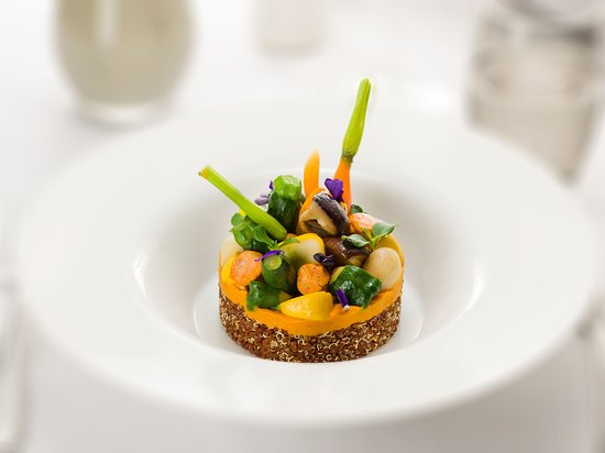 Vegan main course: Vegetables, young spinach and mixed mushrooms composition on a white quinoa bed