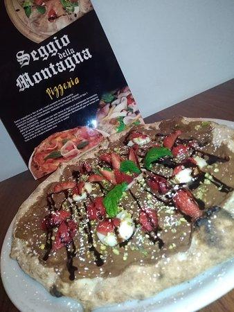 La nostra pizza dessert, condita con: nutella, fragole e granella di pistacchi.
