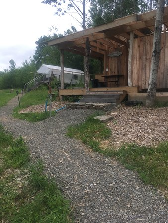 The Meadow @ Shelterbelt Farm: View of the bath house from the parking area, with tent cabin just beyond.