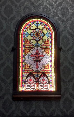 Gothic church style to shop. Backlit stain glass throughout store.