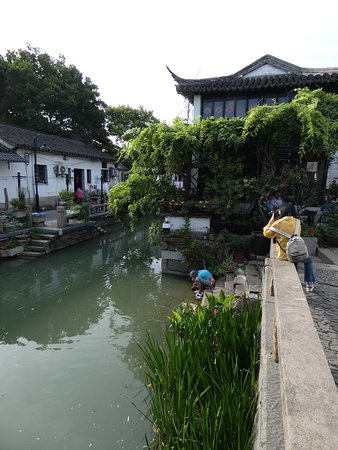 Poverty & prosperity contrasted - elderly woman washing her clothes in the canal