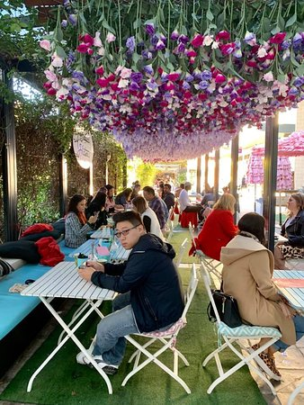 Outdoor eating area with upside down floral arrangement.