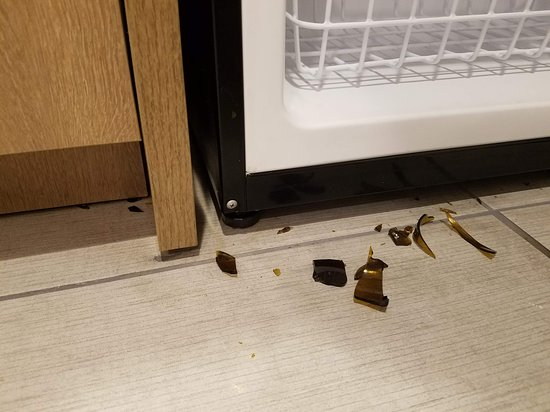 Home2 Suites by Hilton Murfreesboro: Broken glass on the floor in the kitchenette area by the refrigerator that had not been cleaned up.