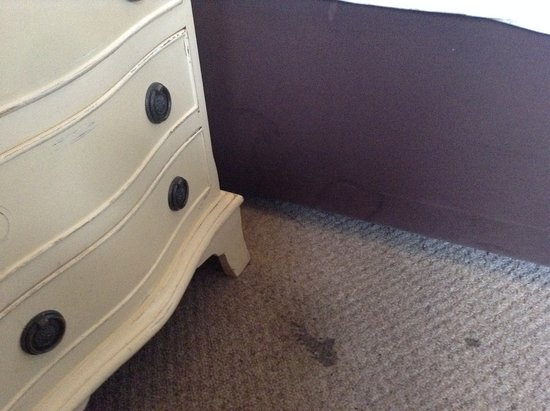 Stain on floor and broken handles on bedside cabinet
