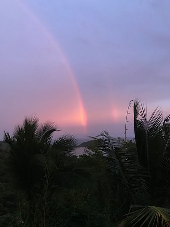 double rainbow ending in the ocean at sunset