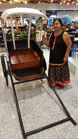 Author's spouse with a life-size model of a hand-drawn rickshaw in Phuket Central Mall.