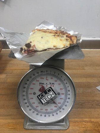 This is a slice of our #15 Meat Lovers. It is our most popular pizza and slice. This slice weighs in at 13 ounces and has a layer of ham, layer of pepperoni and a layer of ground beef topped with an enormous amount of our cheese mix.