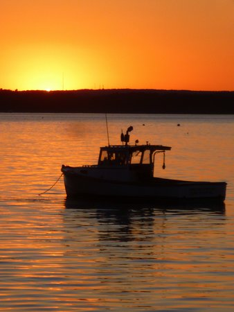 A lobster boat in silhouette is moored off Cleaves Landing just after sunset on Long Island, Maine.