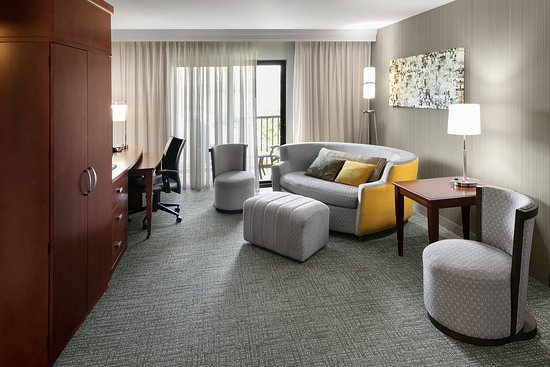 This spacious king suite features a living room area including comfortable chairs and a sofa with ottoman.
