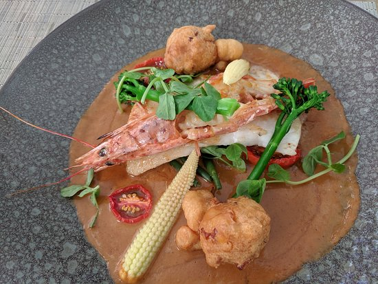 Two Oceans Restaurant: Pan fried Line fish (Kingklip) with sweet corn chilli fritters, tandoori roast shellfish veloute (Langoustine), fine beans, baby garden vegetable.