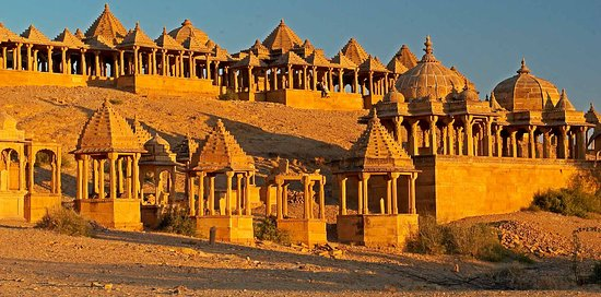 """The Maharajas of Jaisalmer trace their lineage back to Jaitsimha, a ruler of a yadav clan, though Deoraj, a famous prince of the Bhati clan during the 9th century. With him the title of """"Rawal"""" commenced. """"Rawal"""" means """"of the Royal house"""". According to legend, Deoraj was to marry the daughter of a neighbouring chief. Deoraj's father and 800 of his family and followers were surprised and massacred at the wedding. Deoraj escaped with the aid of a Brahmin yogi who disguised the prince as a fellow"""