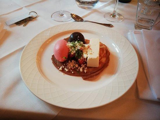 Dessert bestående af en hjemmelavet kiks med en cheesecake med hindbær og hindbærsorbet og friske jordbær, mums