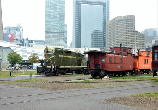 Railway museum exhibits against the buildings of misty Downtown Toronto.