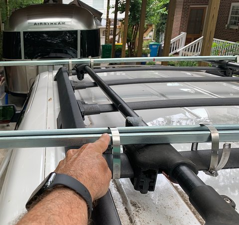"""DIY extended width (84 inches) """"flat rack"""" to stow two inverted Nucanoe kayaks side by side.  Made from heavy duty electrical conduit brackets strapped to existing roof rack via SS adjustable pipe clamps."""