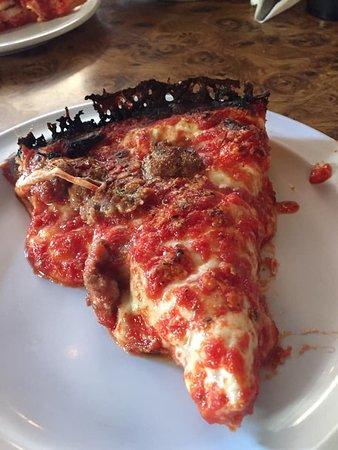 a slice of Burt's Deep Pan with sausage