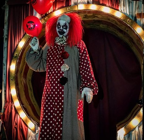 Step past the clown and through the door.
