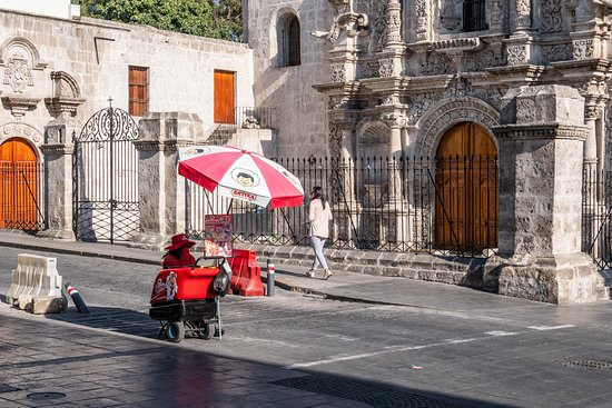 Old and new: a street vendor in front of an old church in Arequipa