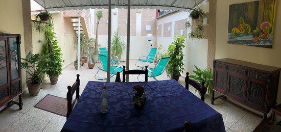 Comedor en el exterior al estilo colonial cubano. Pinturas en óleo de artistas locales decoran las paredes.