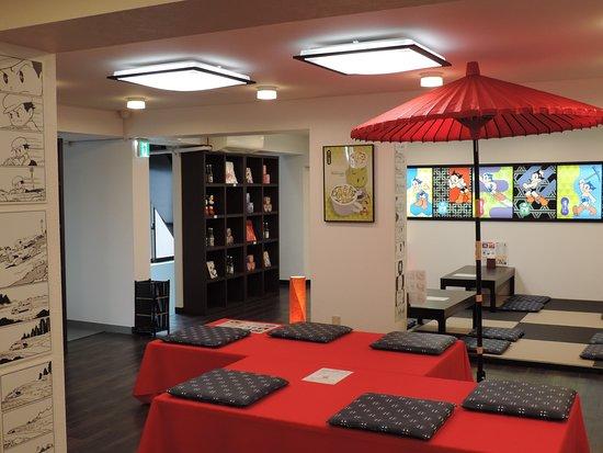 Atomdo Hompo Tezuka Osamu Shop & Cafe: 「アトム堂本舗」の2Fカフェ。畳の席と、番傘の腰掛席、カウンター席がある。壁には漫画のコマがあしらわれている。カフェのメニューに沢山キャラクターが使われていてコースターは持ち帰り可能。wi-fiを経由して手持ちのスマートホン、タブレットで漫画が読めるサービスも提供されている。BGMは手塚アニメ楽曲。