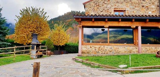 Zona frontal de la masía, con grandes ventanales en el restaurante con vistas al Puigmal.