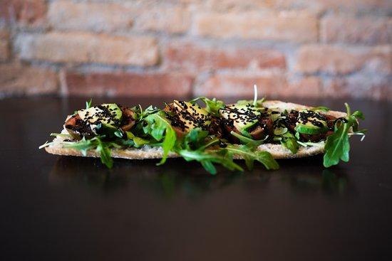 Torrada vegetal con rúcula, rodajas de tomate, aguacate y sésamo negro. Finalizada con reducción de vinagre de Mòdena.