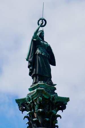 Siegessäule: 戦勝記念塔の頭頂部に、右手に月桂冠を捧げる剣、左手に細長い盾を持つブロンズ像が立つ。
