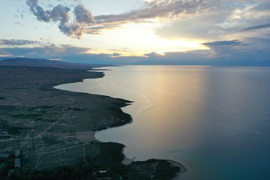 """Bokonbayevo, Δημοκρατία της Κιργιζίας: Issyk-Kul is an endorheic lake in the northern Tian Shan mountains in eastern Kyrgyzstan. It is the tenth largest lake in the world by volume (though not in surface area), and the second largest saline lake after the Caspian Sea. Issyk-Kul means """"warm lake"""" in the Kyrgyz language; although it is surrounded by snow-capped peaks, it never freezes.  Issyk-Kul Lake is 182 kilometres (113 mi) long, up to 60 kilometres (37 mi) wide, and its area is 6,236 square kilometres (2,408 sq mi). It is the seco"""