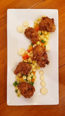 Hushpuppy crusted oysters, plump and juicy with Citrus aioli, over sweet corn and pea succotash
